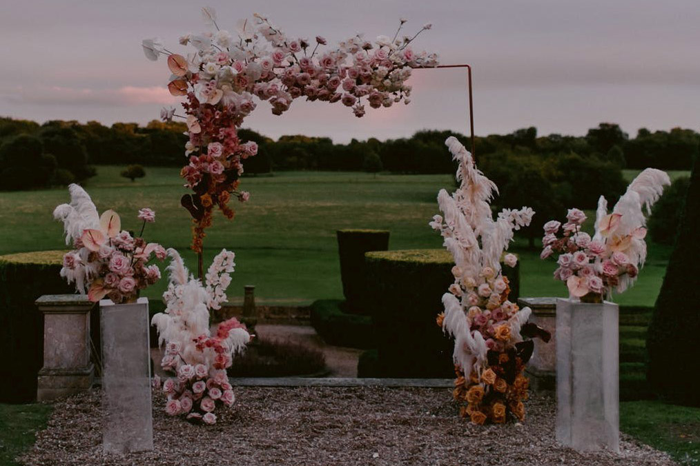 Hosting a micro wedding: Image of ceremony arch with bohemian style flowers