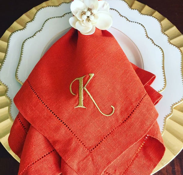 Photo of orange monogrammed napkin on china